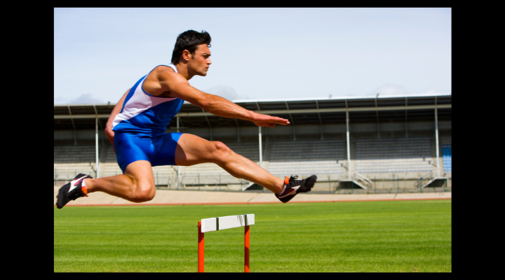 Track athlete jumping over a hurdle