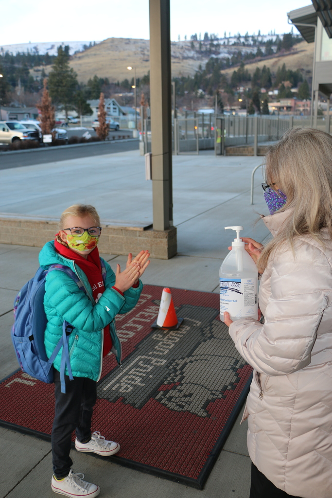 Hadley Wolcott rubs sanitizer between her hands before entering the building.